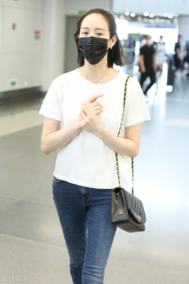 张钧甯图片,张钧甯戴黑色口罩,穿白色T恤搭配牛仔裤,脚踩平底鞋,休闲随性